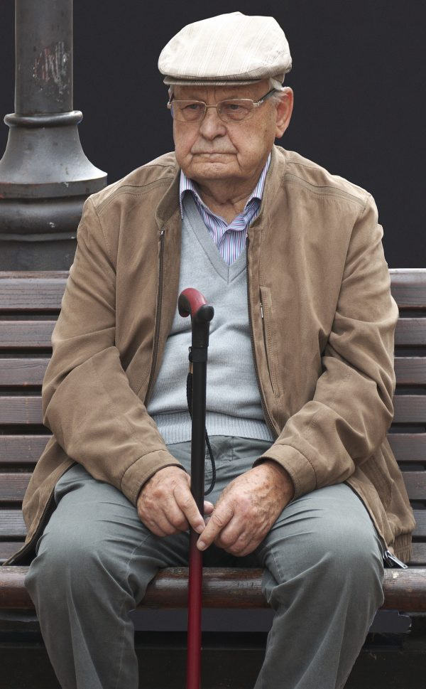 Back pain for the elderly, old man with walking stick sitting down