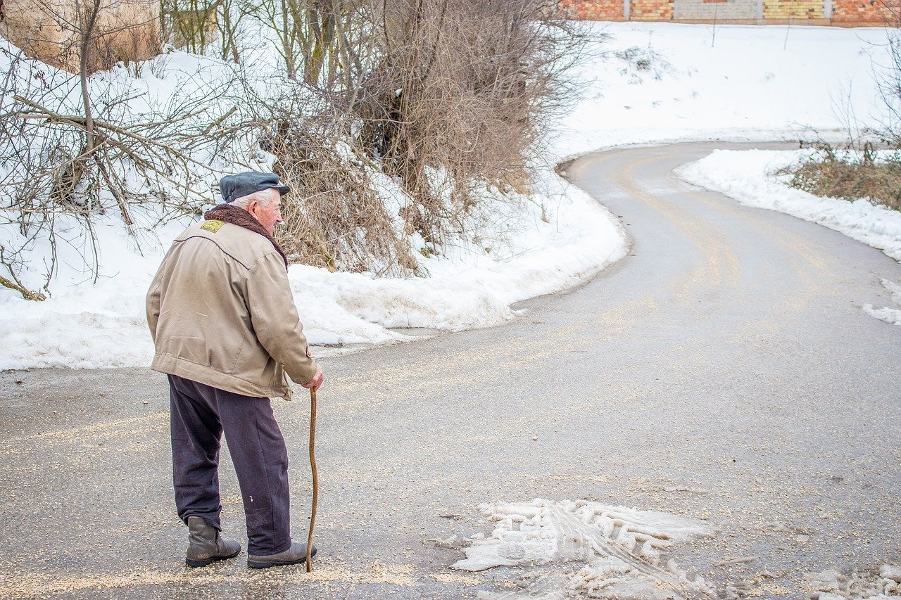 January blues for the elderly, old man walking alone in the snow